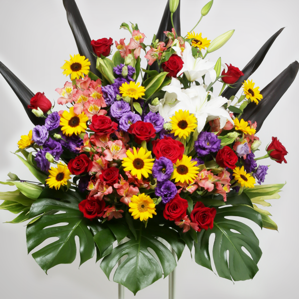 スタイル:華やか 色味:おまかせ 備考:カラフルひまわりとバラをメインにしたカラフルな構成。4種のグリーンを合わせたスタンド花。 20,000円